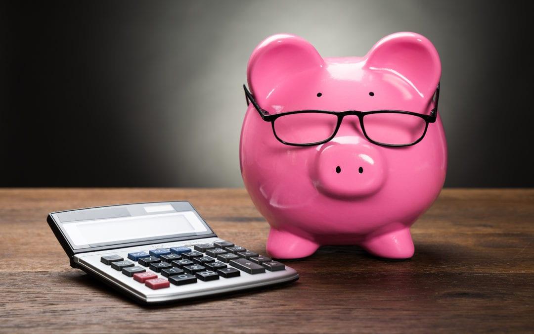 pink piggy bank next to calculator