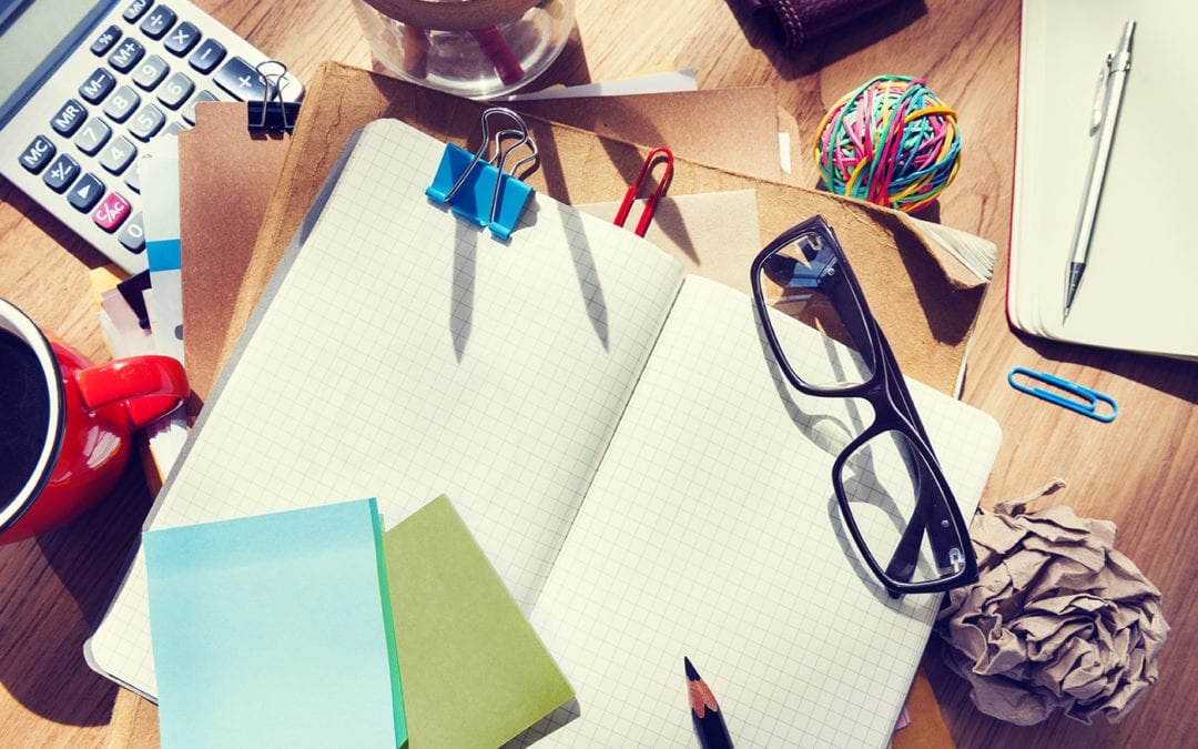 a messy desk with notebooks, glasses, a calculator and other items