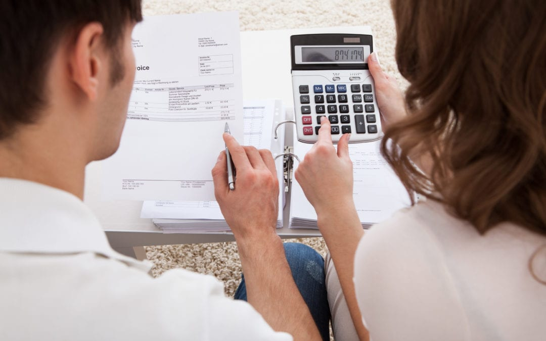a couple reviewing an invoice with a calculator