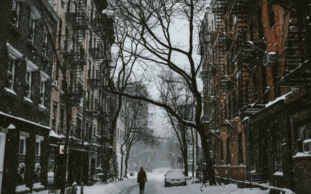 a snowy street with apartments on both sides